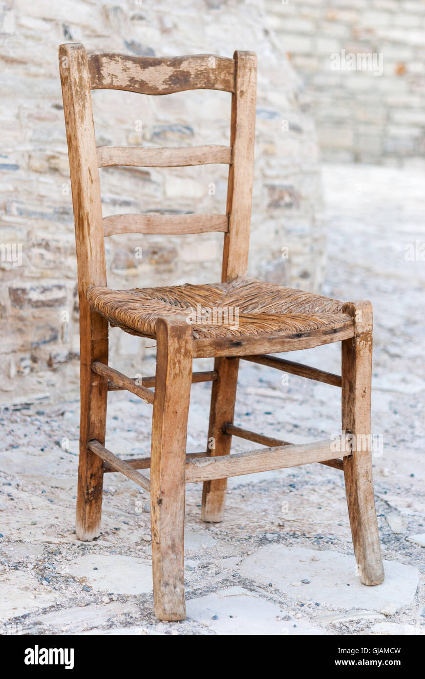 Old Shabby Wooden Straw Chair With Cobblestone As A Background Closeup.