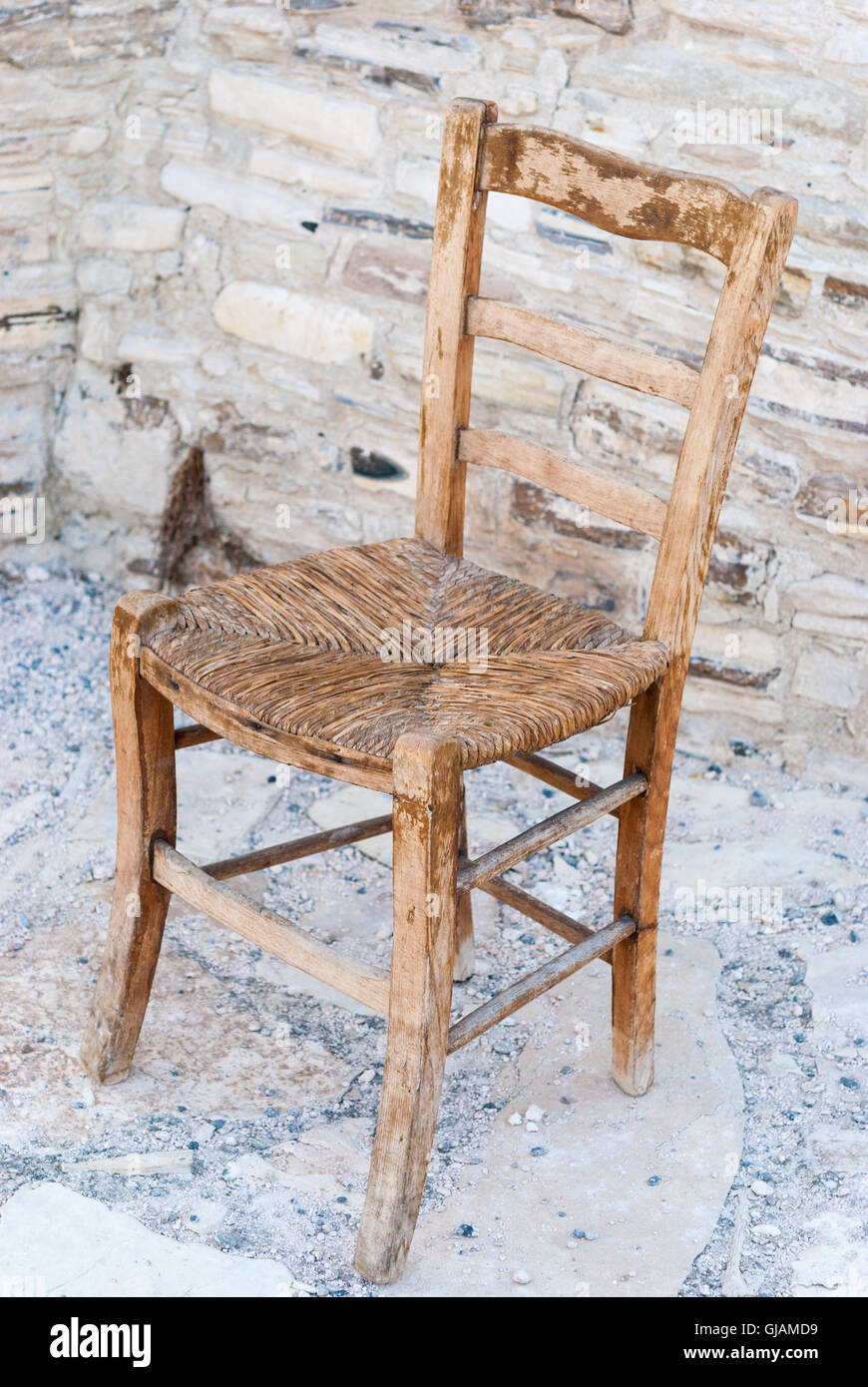 Delicieux Old Shabby Wooden Straw Chair With Cobblestone As A Background Closeup.