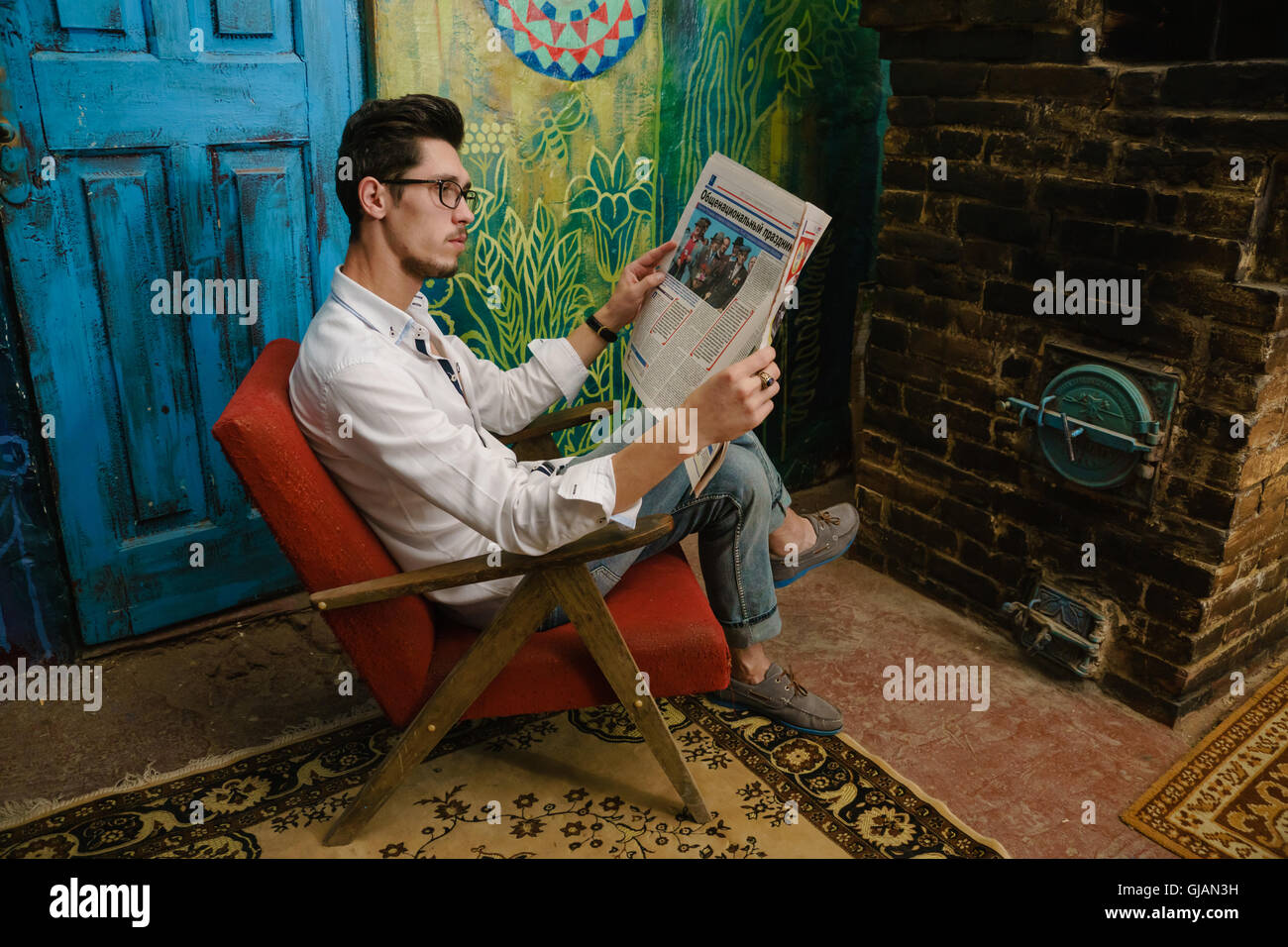 thoughtful reading of young man on the old armchair beside unusual wall - Stock Image
