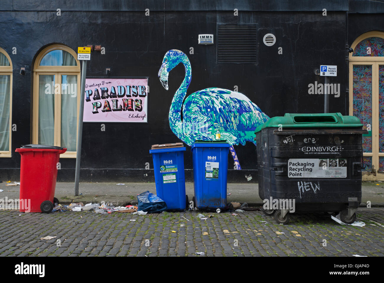 Waste bins and rubbish on the street to the side of the ironically names Paradise Palms venue in Edinburgh. - Stock Image