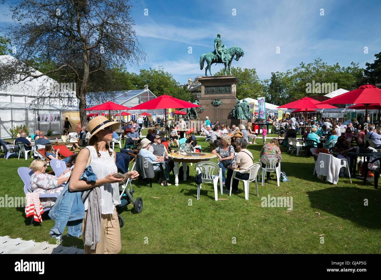 Visitors to the annual Edinburgh Book Festival enjoying the sunshine in Charlotte Square. - Stock Image