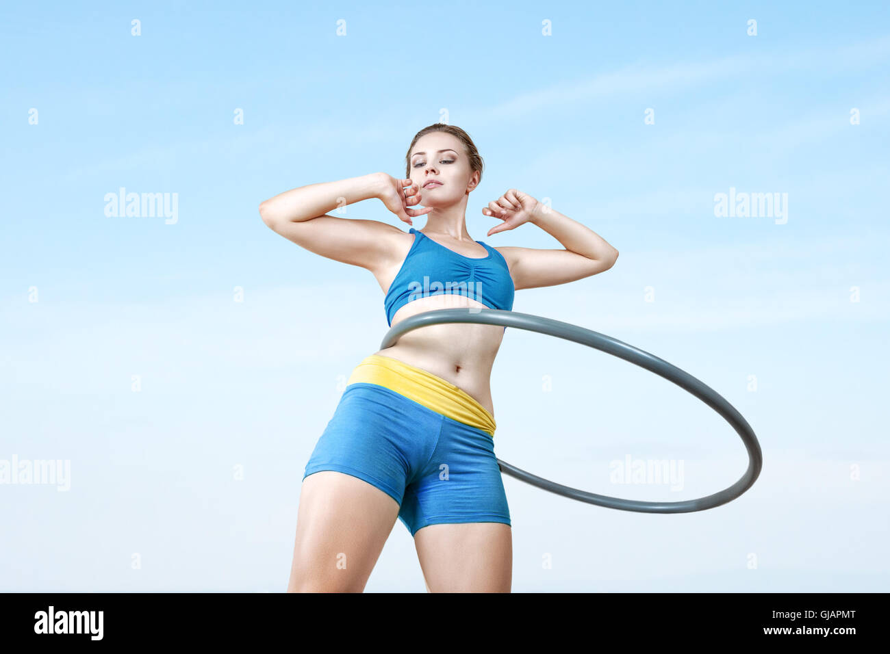 Young woman rotates hula hoop on nature background. Low angle view - Stock Image