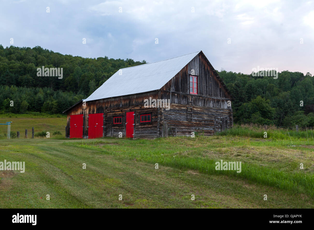 Barn with red doors and windows in Quebec - Stock Image