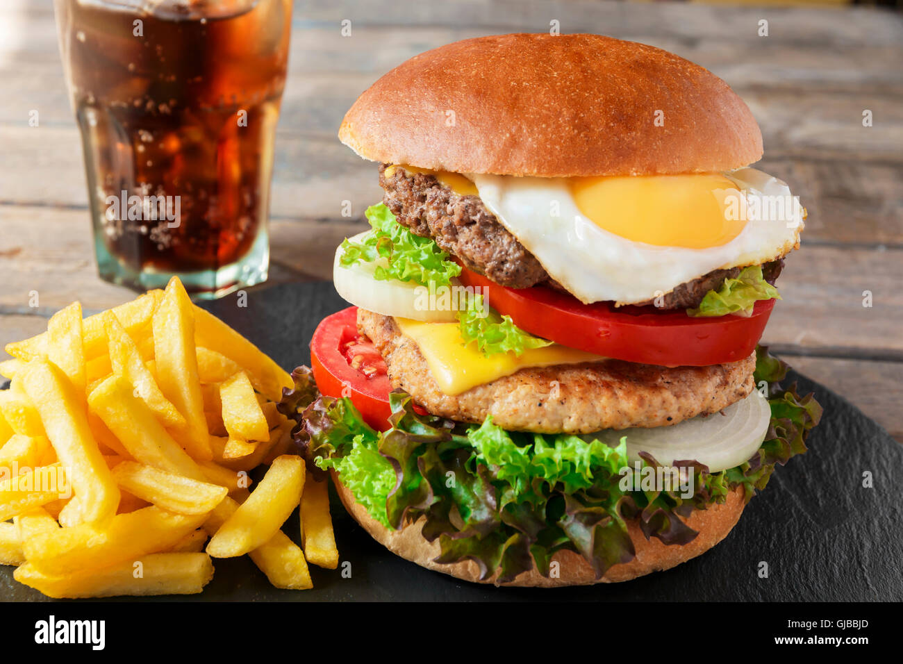 hamburger meat cutlet egg cheese french fries - Stock Image