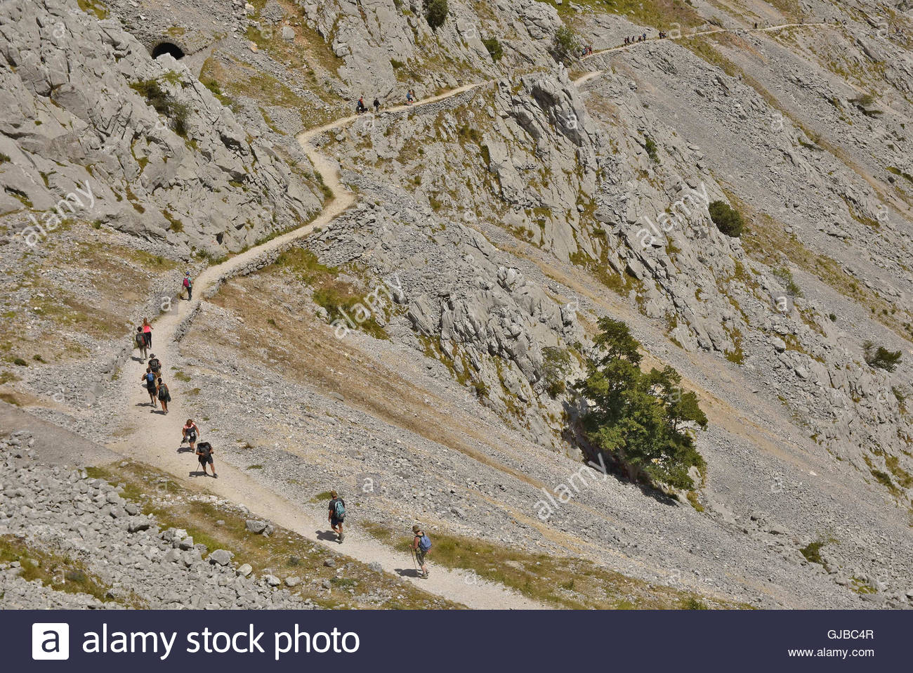 Hikers walking along Cares Gorge route between towns of Cain and Poncebos, Picos De Europa National Park Northern - Stock Image
