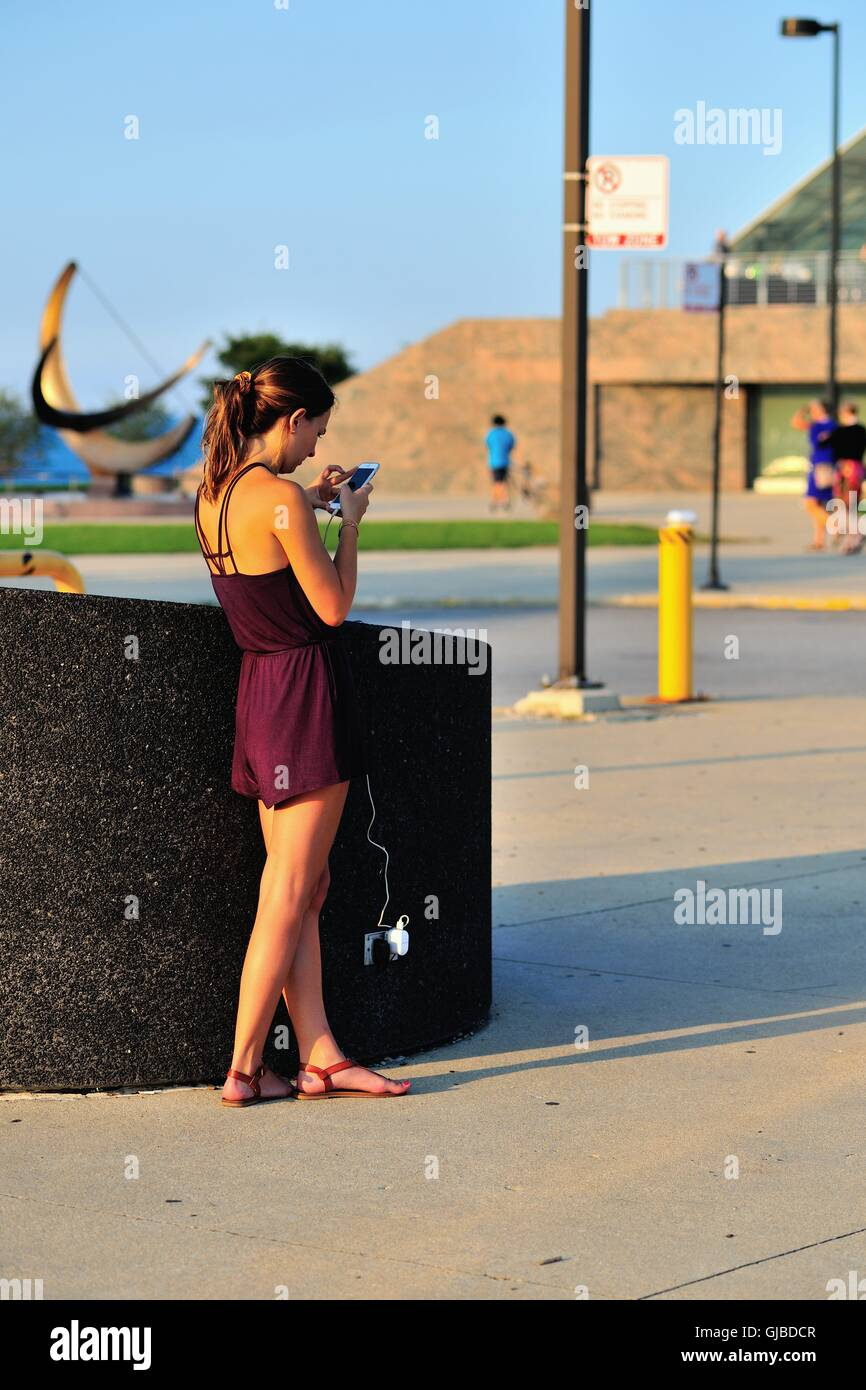 A young woman takes advantage of an outdoor electrical outlet to recharge her cell phone while also using the device. - Stock Image