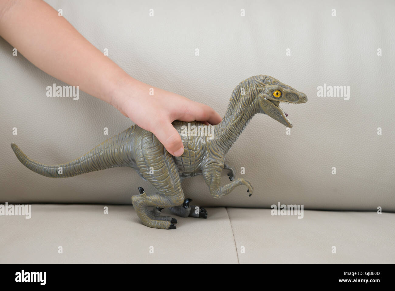 kids hand catching a greu Deinonychus toy on a sofa at home - Stock Image