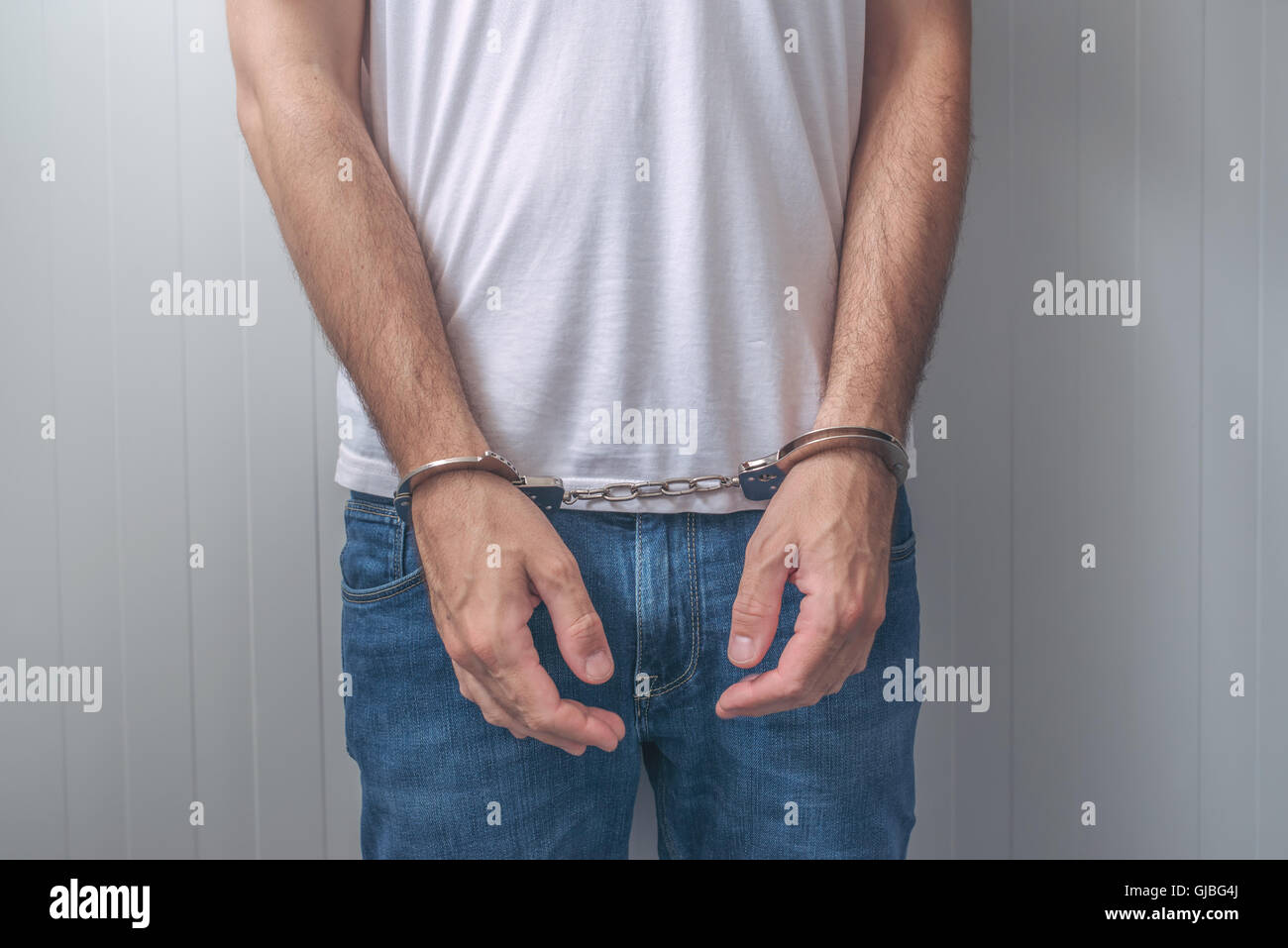 Arrested man with cuffed hands. Unrecognizable male person in jeans with handcuffs held in police station for being - Stock Image