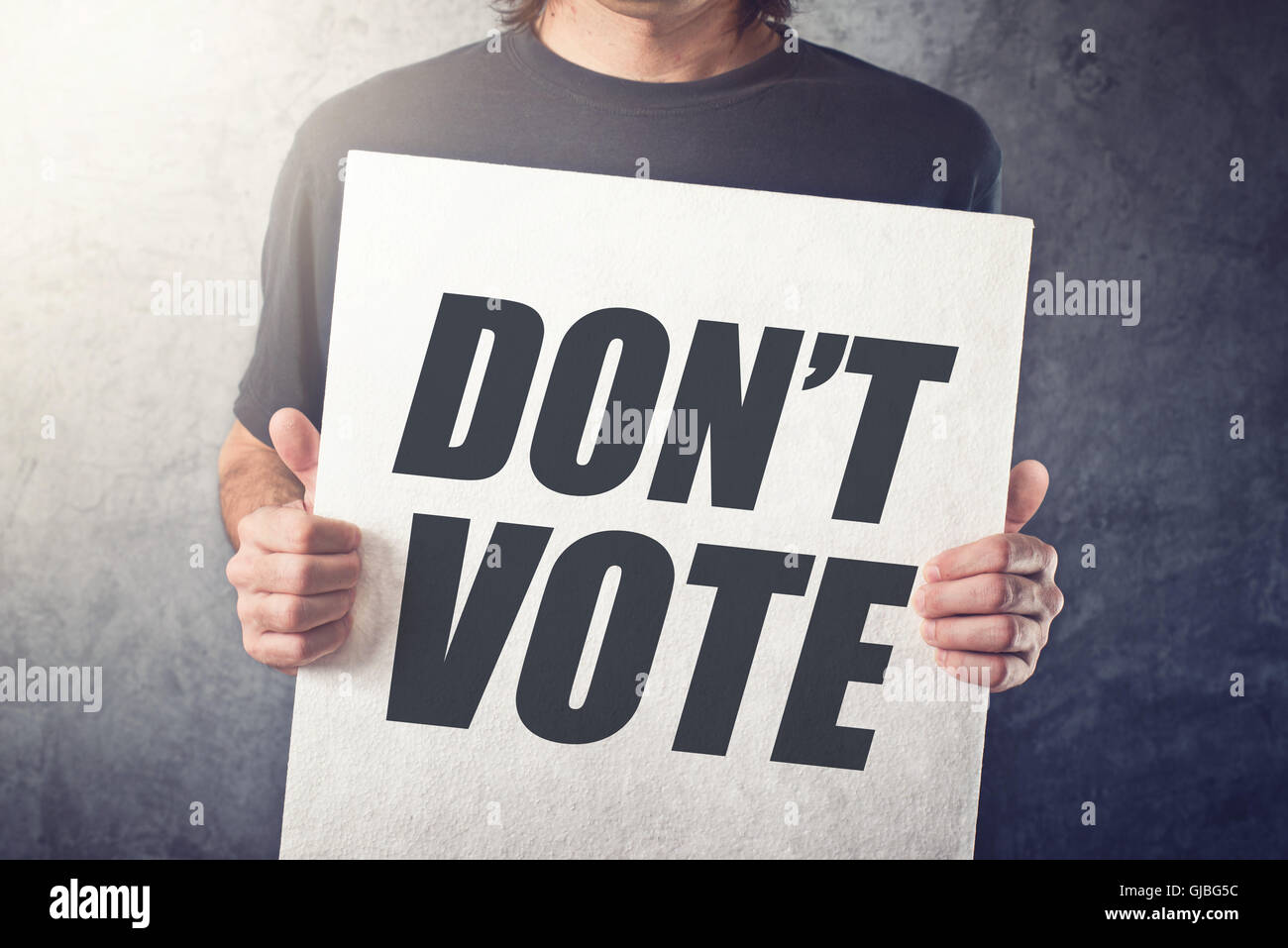 Man holding poster with Don't vote title printed on chest, express attitude and opinion on political elections Stock Photo