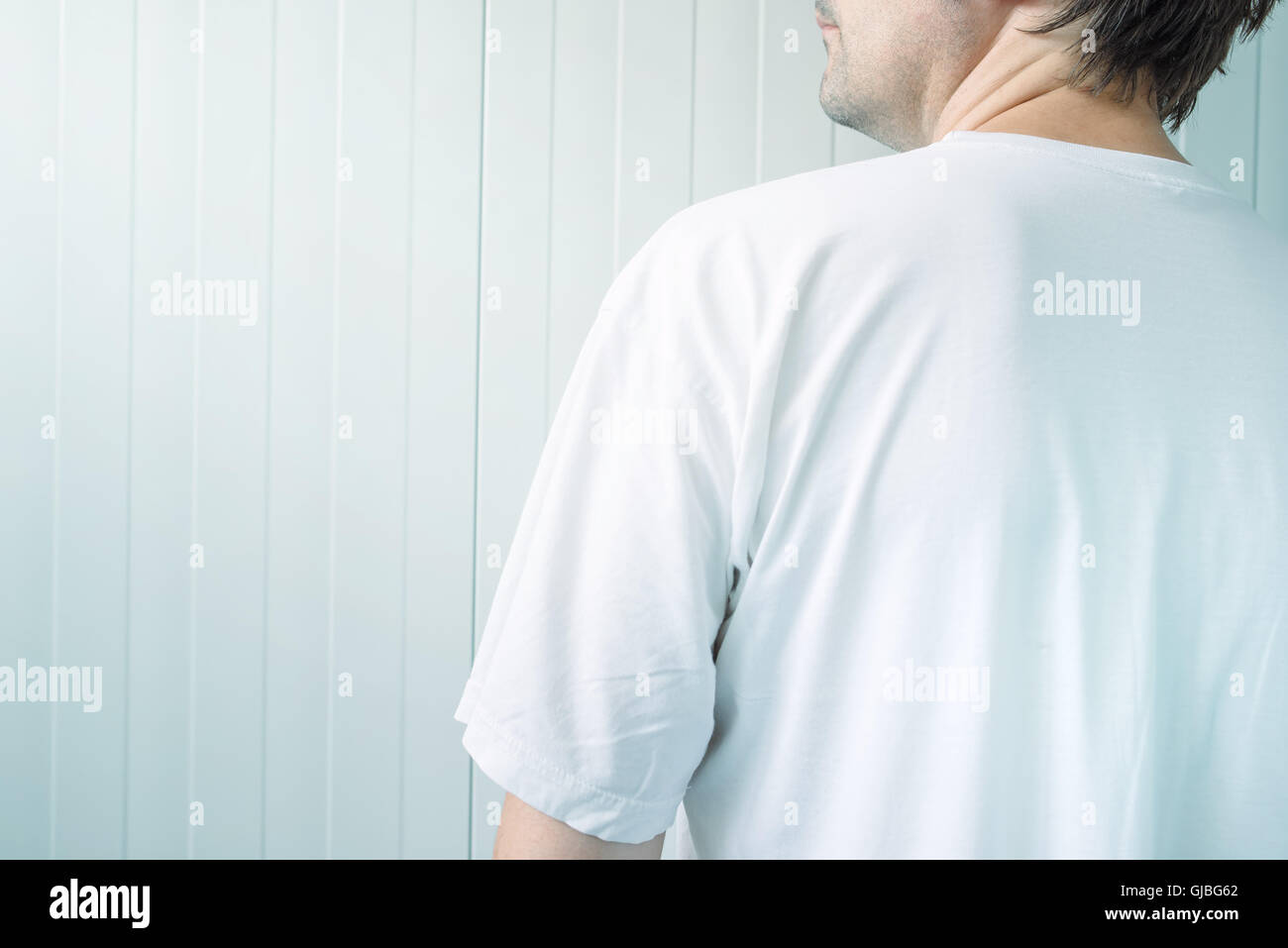 Man in white shirt from behind, blank male t-shirt as copy space for mock up graphic design or text - Stock Image