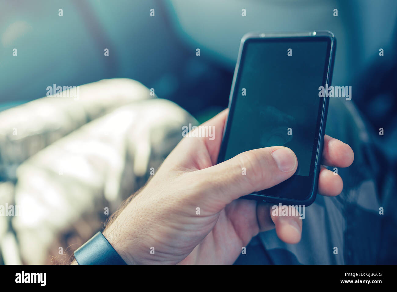 Playing with mobile phone instead of his child, bad role model father using smartphone while his son asks him to - Stock Image