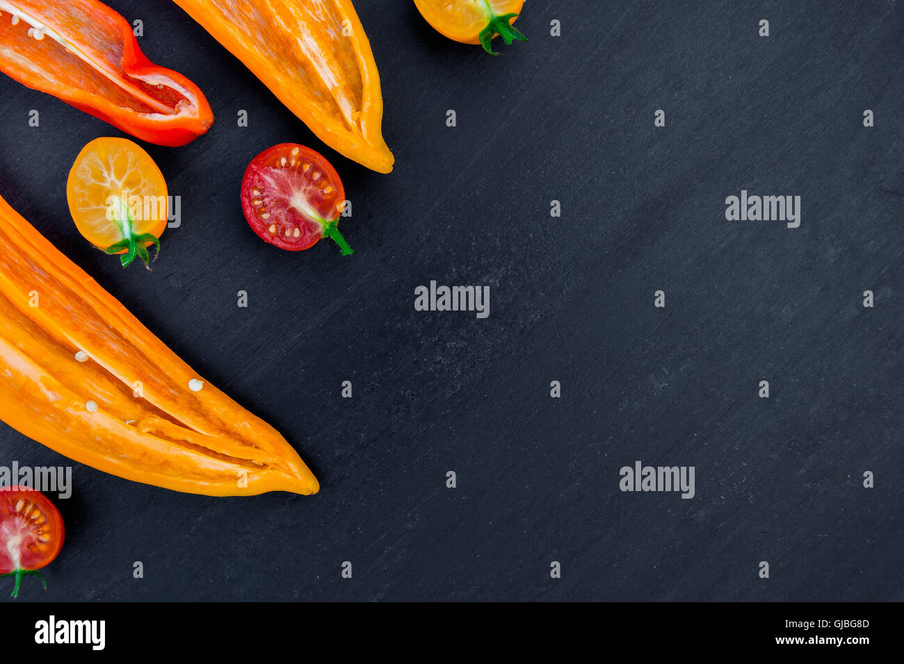 Mixed of half red and yellow pepper with a green branch near cherry tomato on a black backround. Top view. Frame. - Stock Image