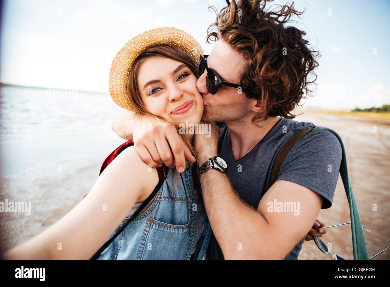 Happy young couple kissing and taking selfie outdoors - Stock Image