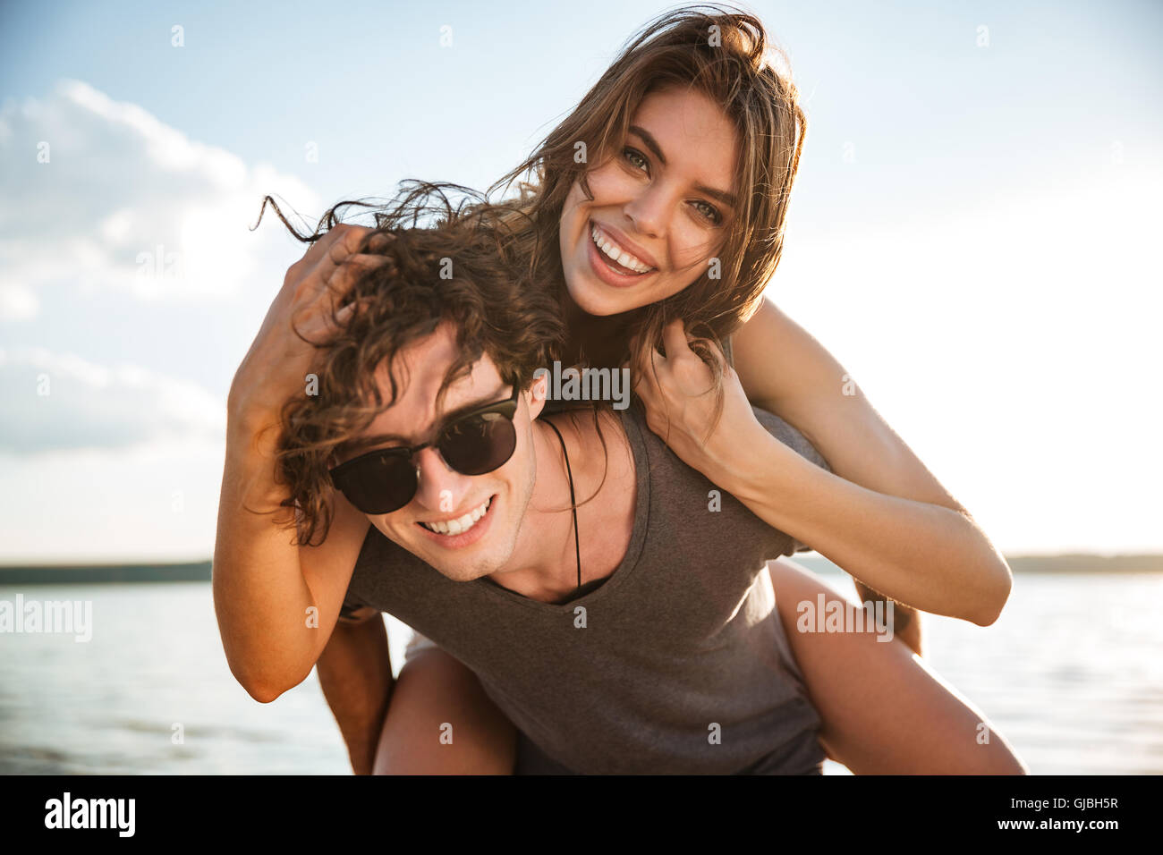 Young happy smiling couple in love piggyback at the beach - Stock Image