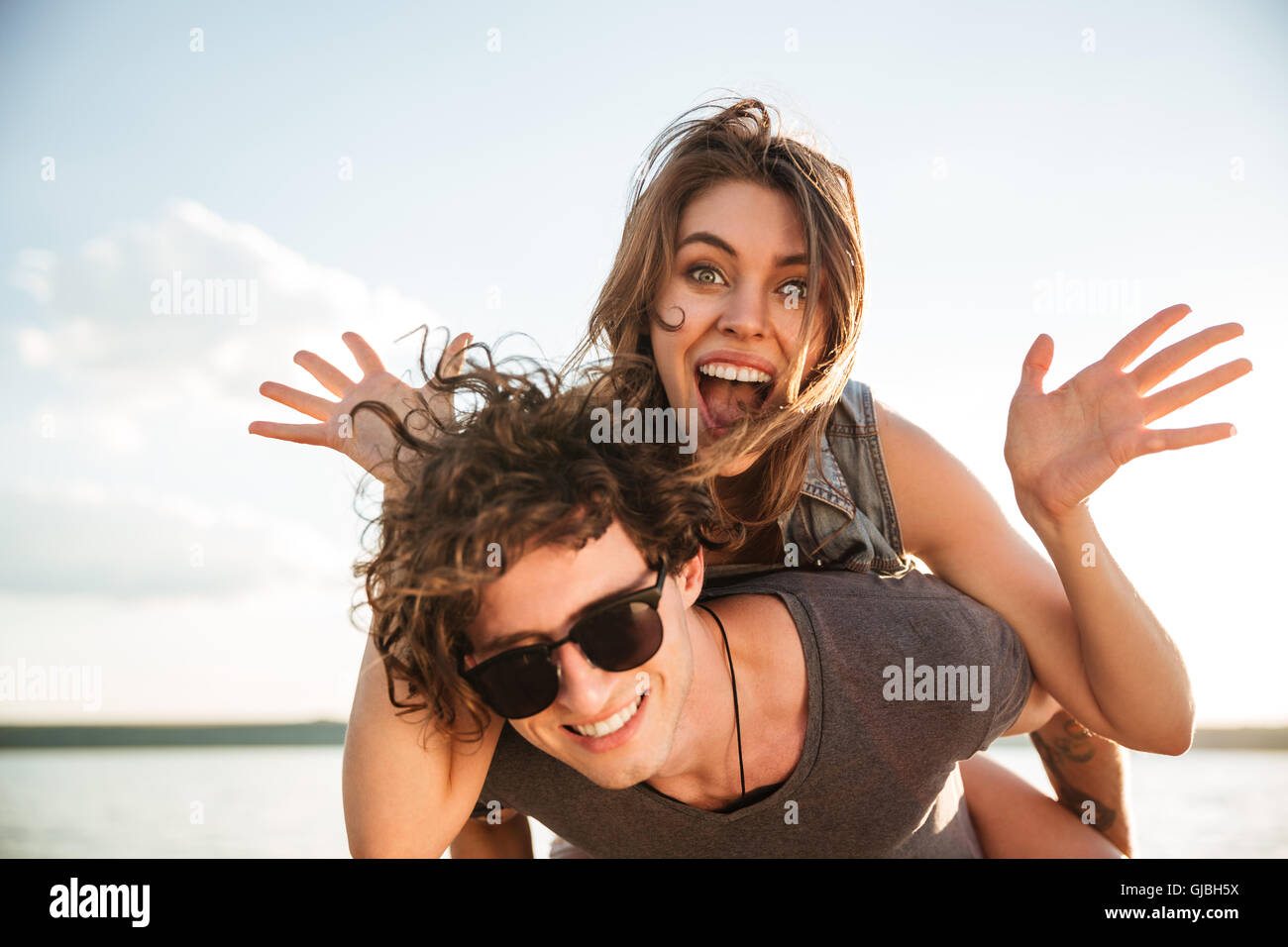 Young happy smiling couple in love piggyback at the beach, cheerful girl is screaming - Stock Image