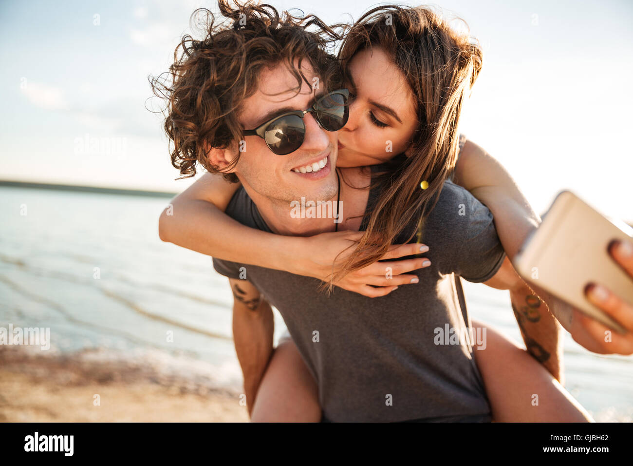 Young happy couple in love kissing and making selfie at the beach, piggyback ride - Stock Image