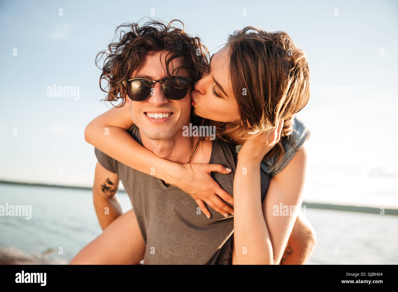 Young man giving piggyback ride to girlfriend by the ocean Stock Photo