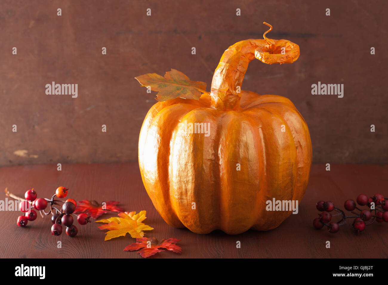 decorative golden papier-mache pumpkin and autumn leaves for halloween thanksgiving - Stock Image