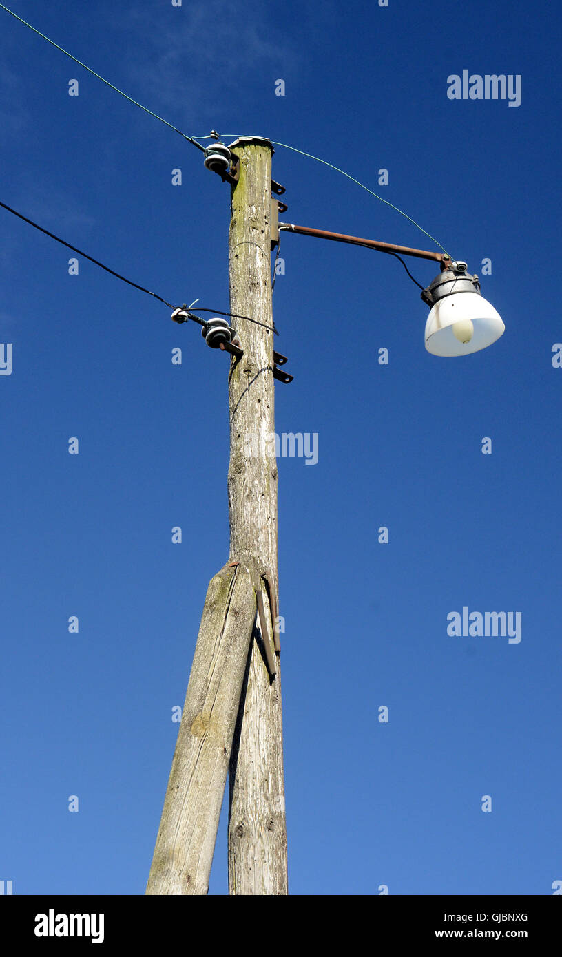 old wooden lamp post with light bulb and overhead wires they use