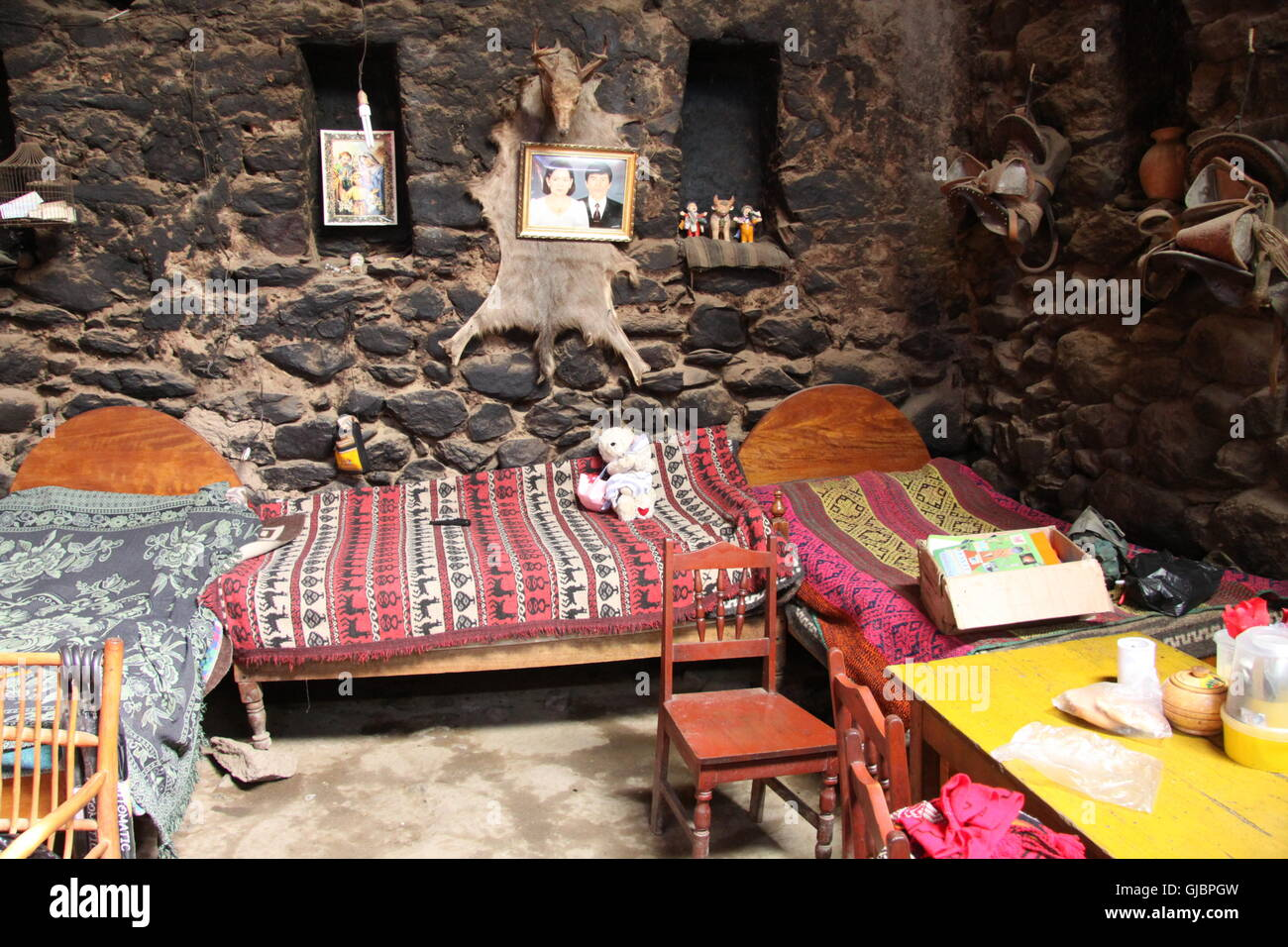 Traditional Peruvian primitive dwelling in Urubamba, with dried mud floor, and colourful bedding and religious artefacts - Stock Image