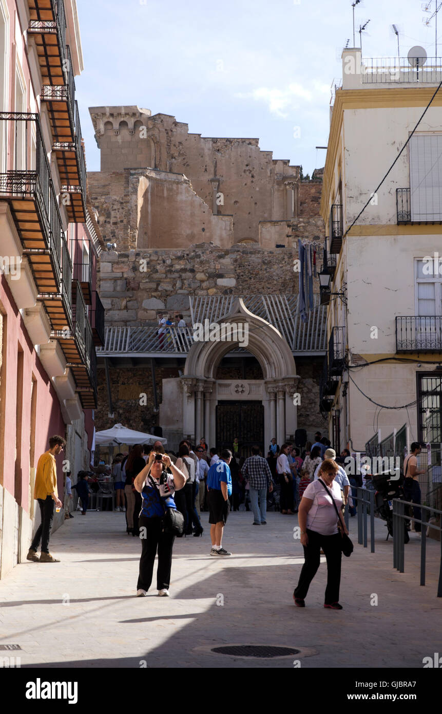 Tourist wander by modern buildings, ancient Roman theater ruins rise up behind the buildings. - Stock Image