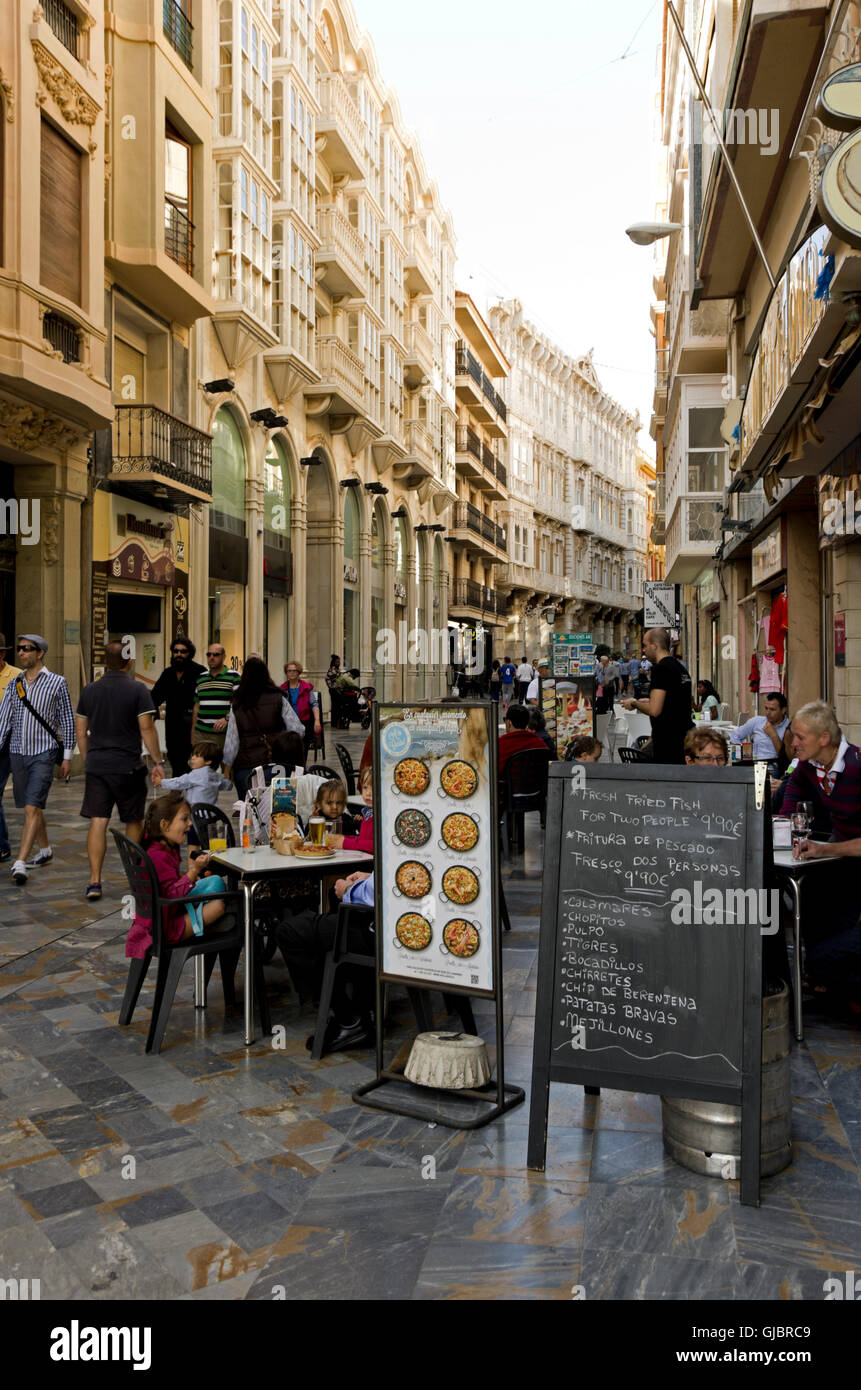 Tourist eat lunch out doors, sandwich board showing 8 types of paella - Stock Image
