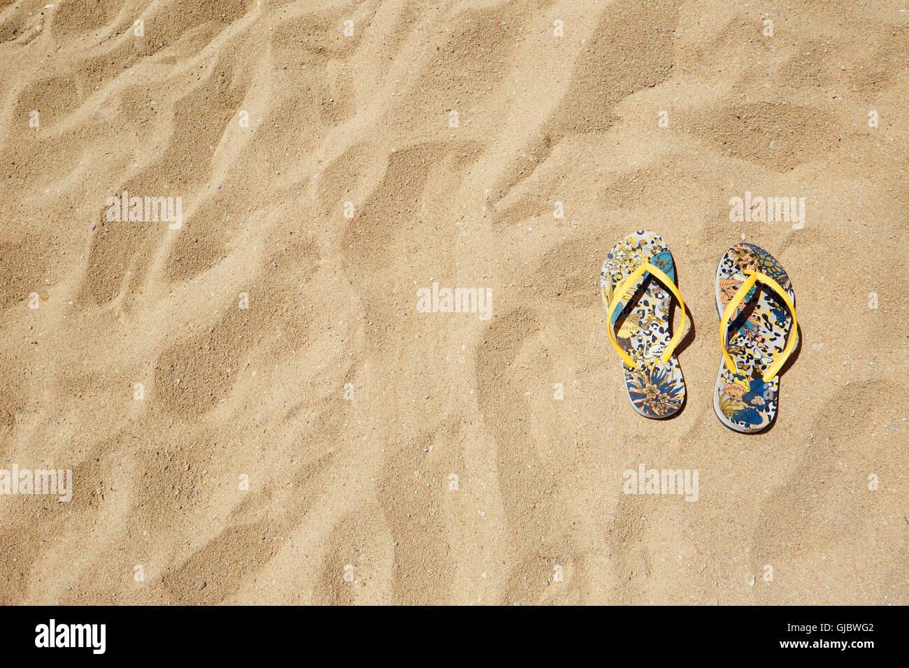 Closeup Beach Sandals Flip Flops or Tongs Sandy  Background Copyspace. Summer Concept. Horizontal. No body photo. - Stock Image