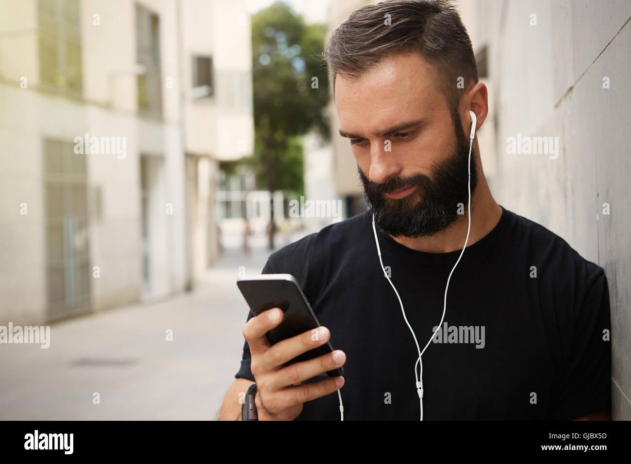 Bearded Muscular Man Wearing Black Tshirt Blank Snapback Cap Summer Time.Young Men Using Smartphone Headphones Looking - Stock Image