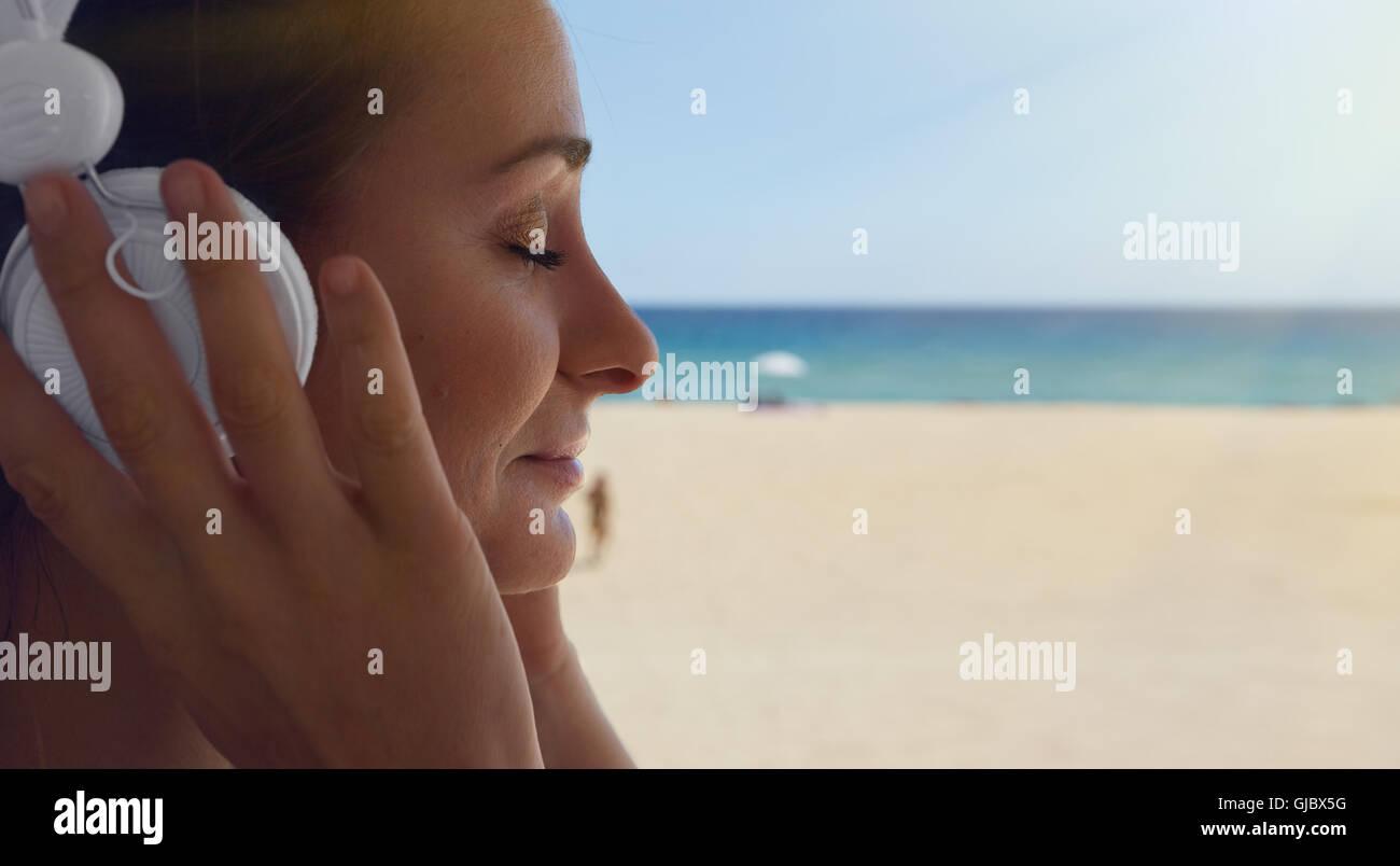 Closeup Portrait Handsome Young Woman Listening Music Player Headphones Sea Beach Background.Pretty Girl Enjoy Audio - Stock Image