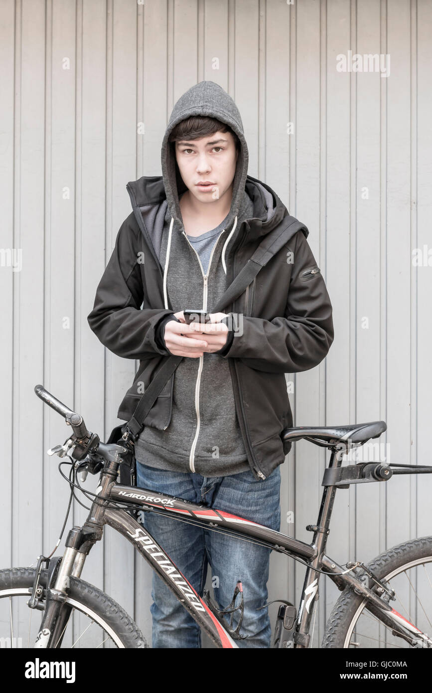 youth by bike and mobile phone in Frankfurt am Main, Hessia, Germany - Stock Image