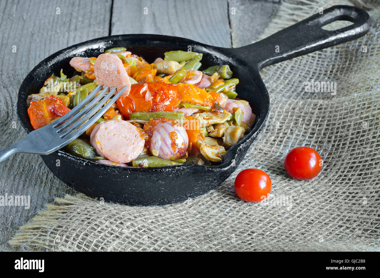Roasted vegetables with sliced sausage. - Stock Image
