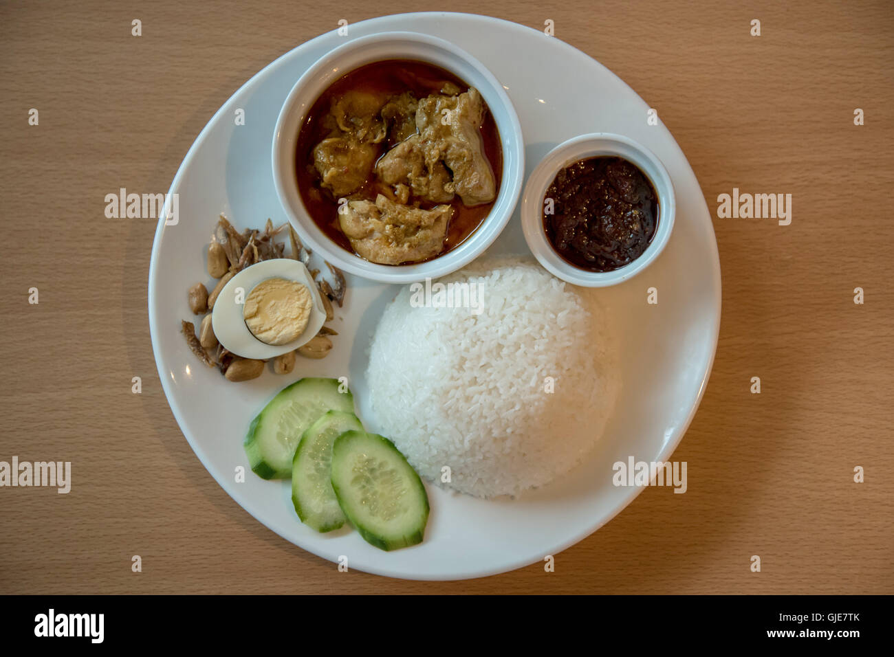 Nasi Lemak with chicken curry, anchovies, boiled egg, spicy sambal and rice - Stock Image