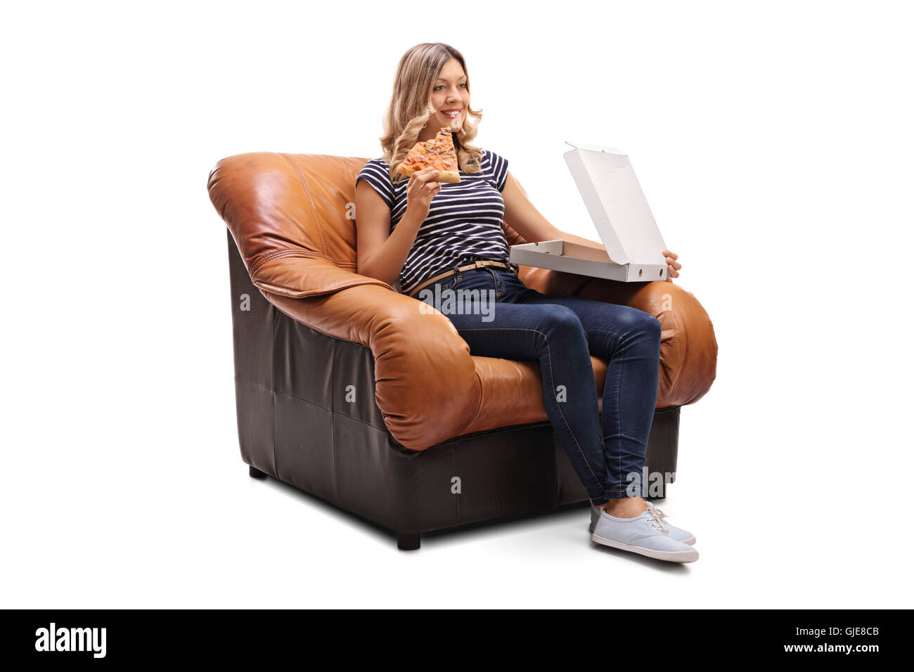 Young woman seated on an armchair having a slice of pizza and watching tv isolated on white background - Stock Image