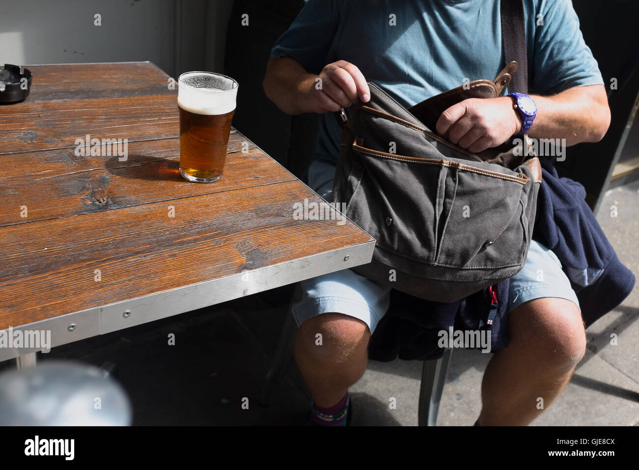 A man takes a break in the sun for a pint. - Stock Image