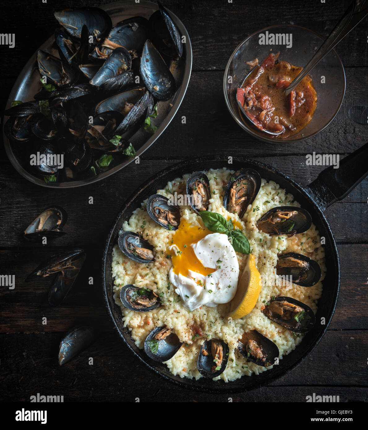 Cooked mussels with boiled egg and rice in the pan on wooden background - Stock Image
