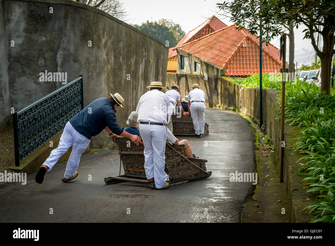 Funchal traditional sledge downhill riders in Monte park. - Stock Image