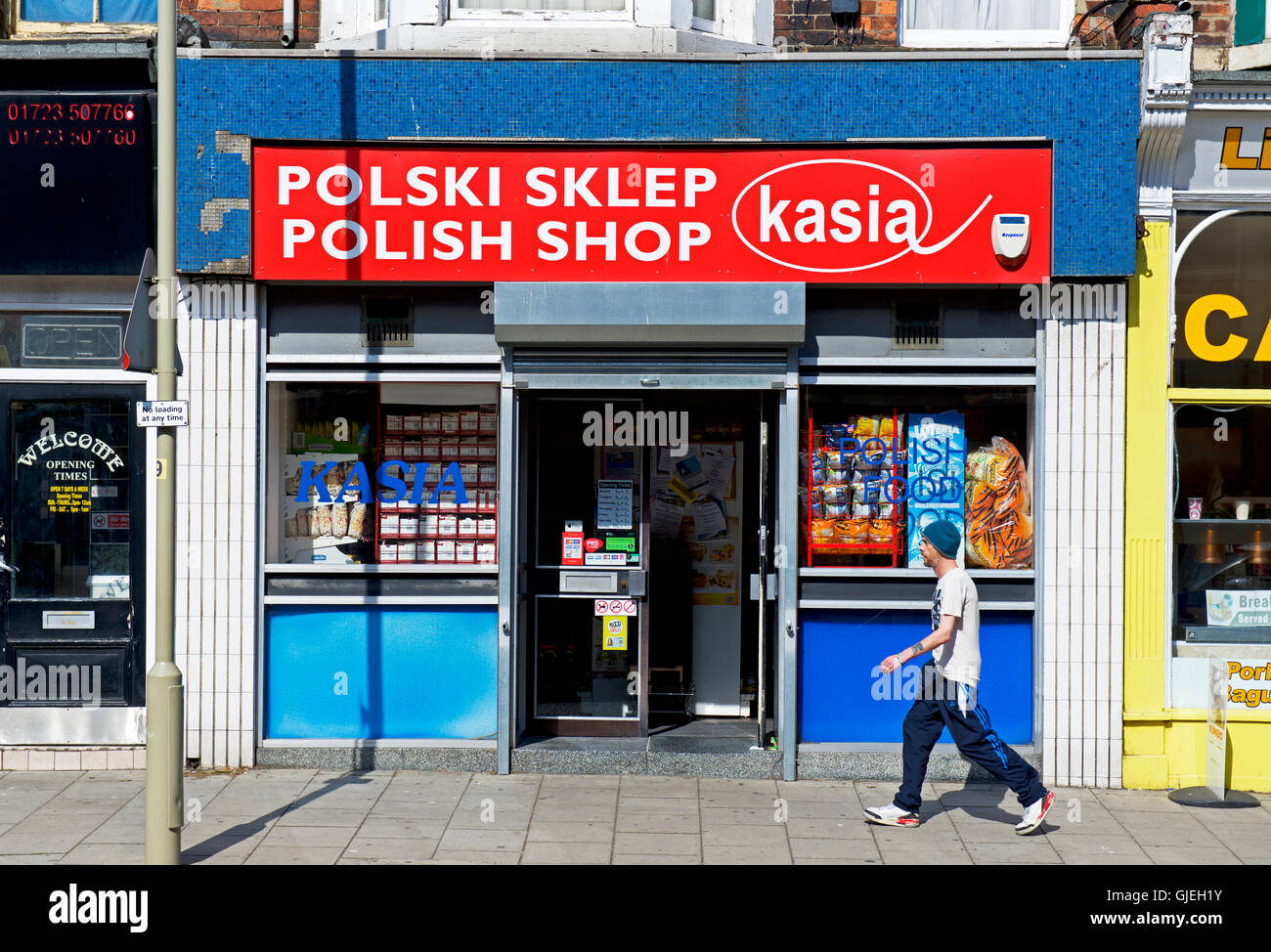 5acf9a934b9a6 Man walking past Polish shop in Scarborough, North Yorkshire, England, UK -  Stock