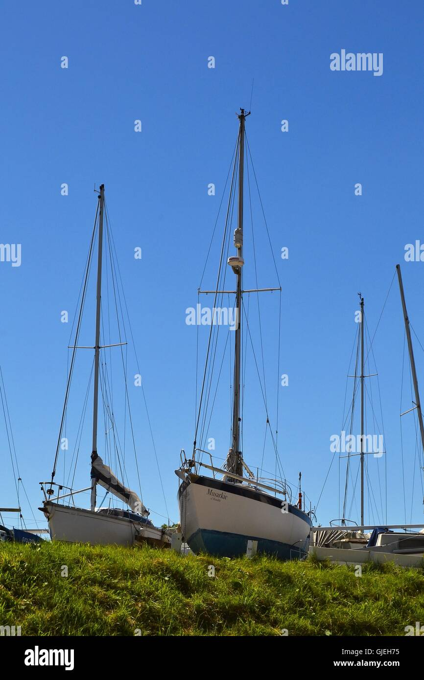 Blue and White Yacht Hulls and Masts in dry dock at Skippool Creek - Stock Image