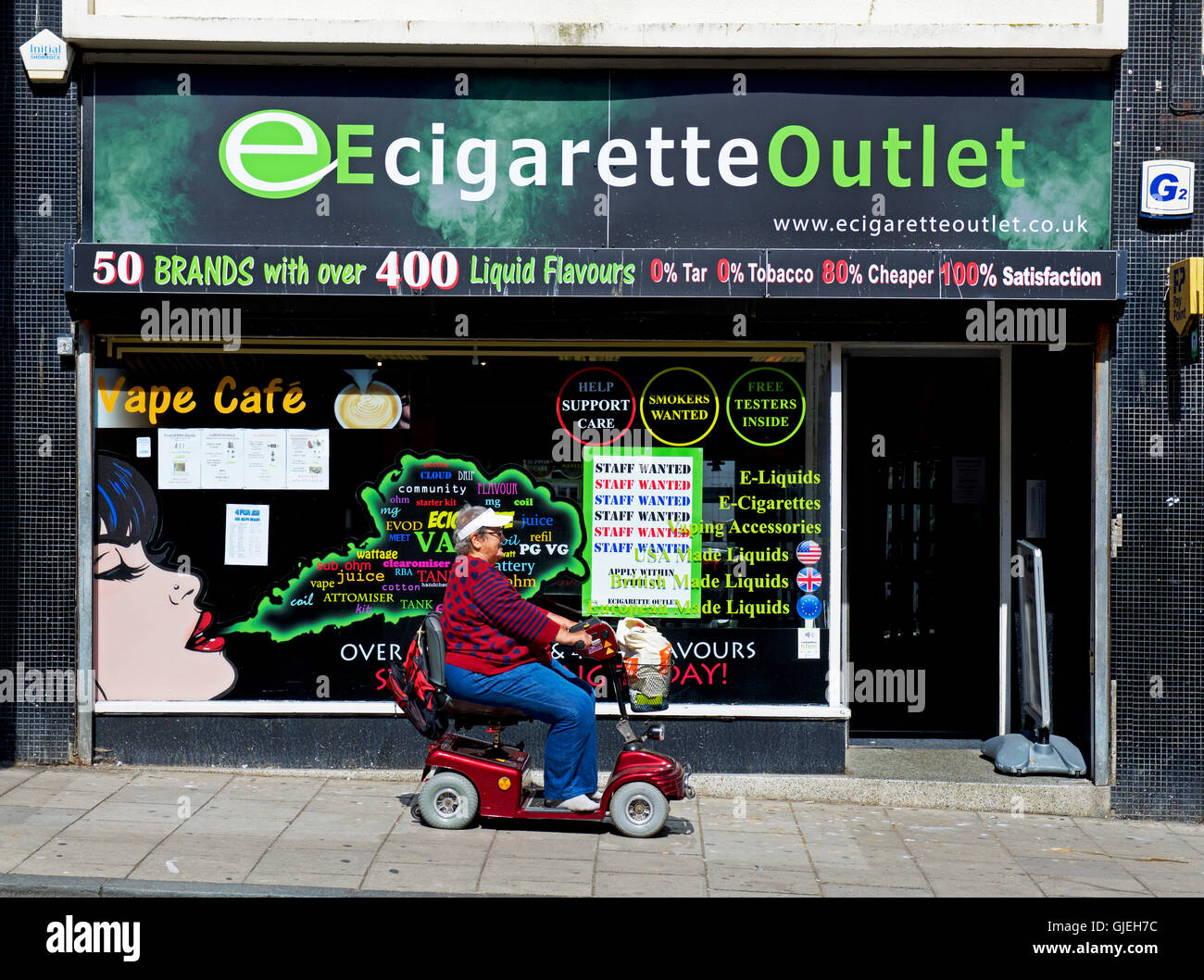 Woman on mobility scooter in front of Ecigarette outlet shop, England UK - Stock Image