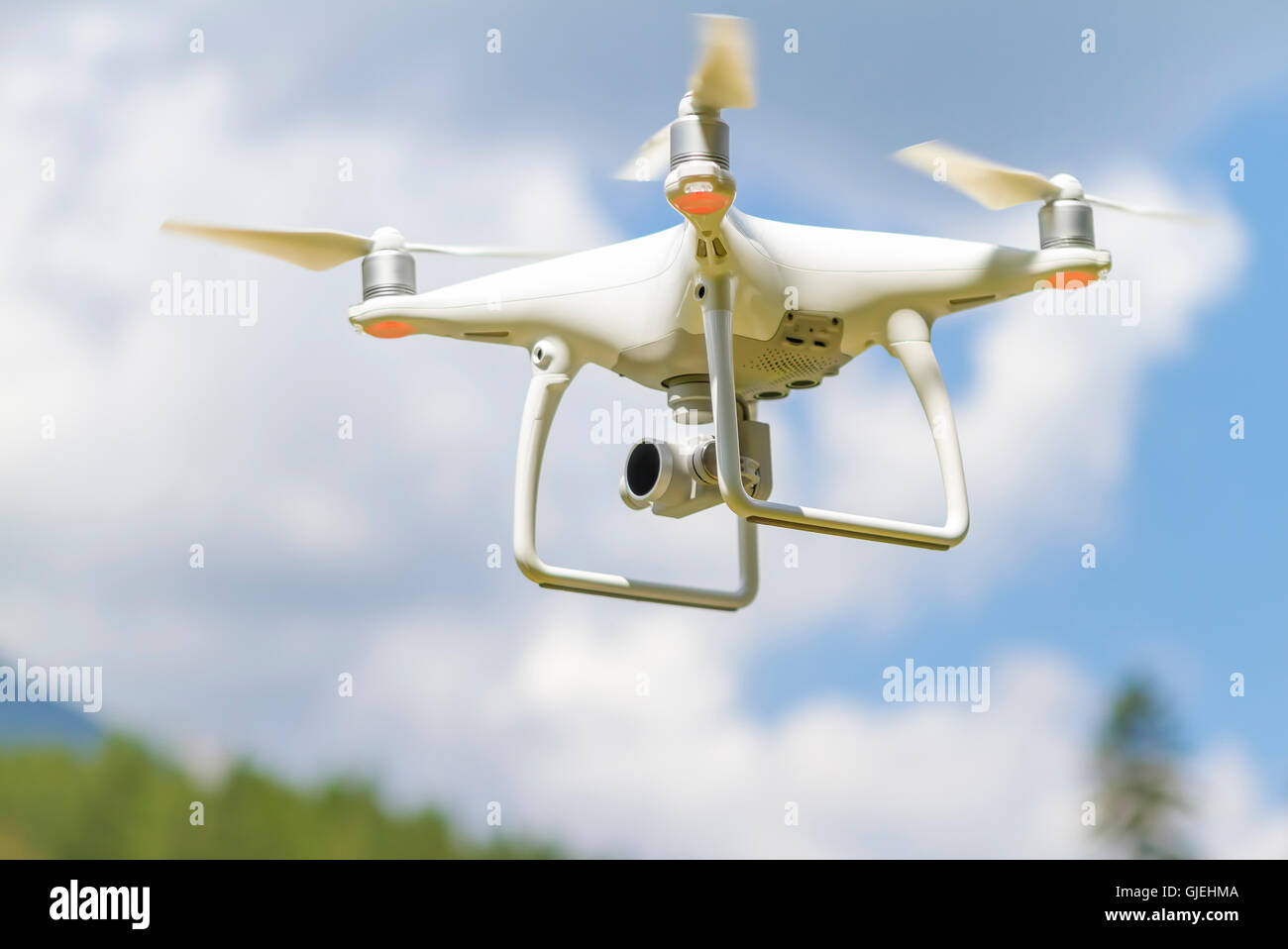 White drone quad copter with high resolution digital camera flying in the blue sky over the mountain - Stock Image