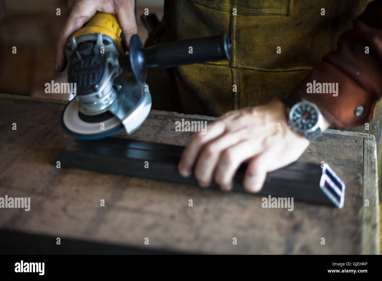 Woodworker grinding metal support structure for table. - Stock Image