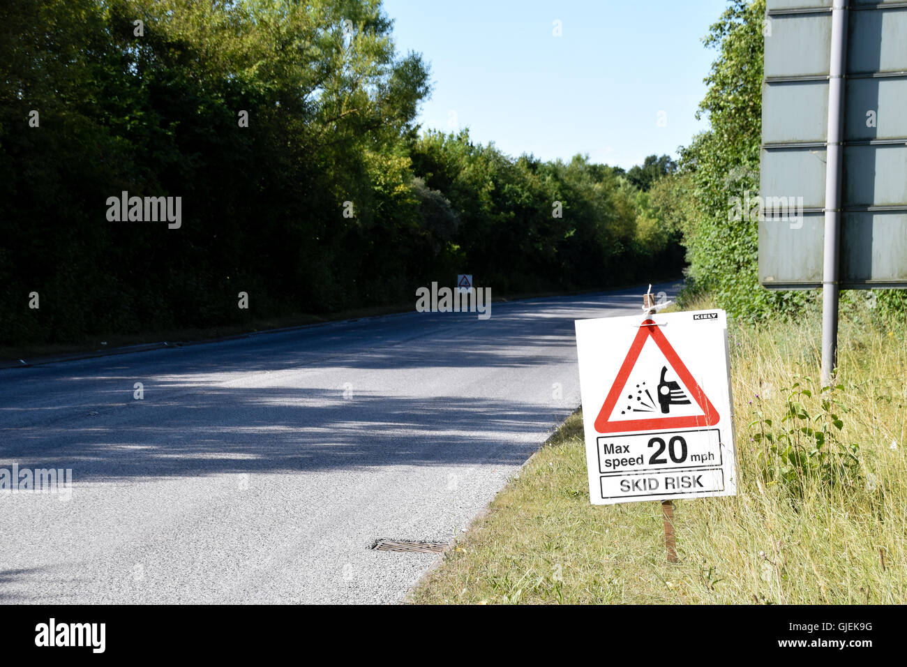 Skid risk warning on newly laid road - Stock Image