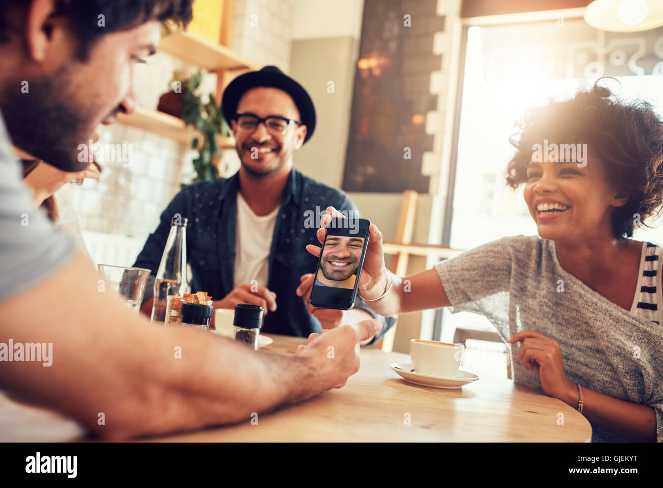 Portrait of happy young friends in cafe and looking at the photos on smart phone. Group of mixed race people sitting Stock Photo