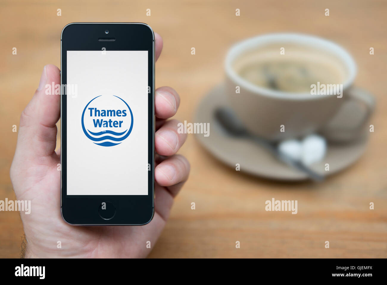 A man looks at his iPhone which displays the Thames Water logo, while sat with a cup of coffee (Editorial use only). - Stock Image