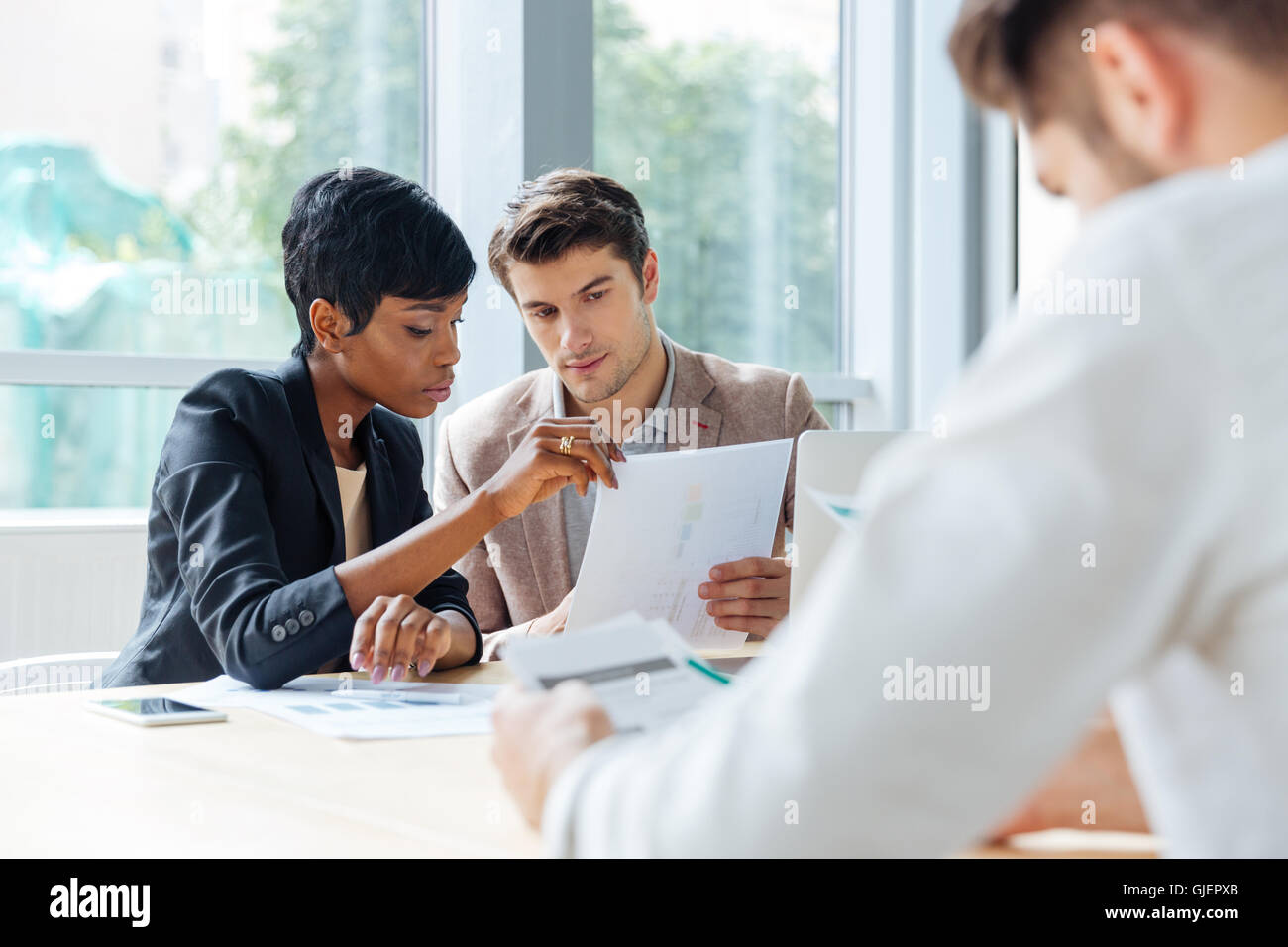 Multiethnic group of young business partners discussing ideas in conference room - Stock Image