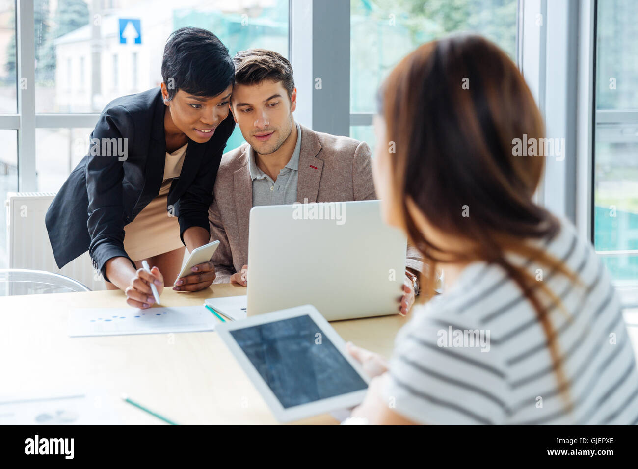 Group of businesspeople working with laptop, tablet and cell phone on business meeting - Stock Image