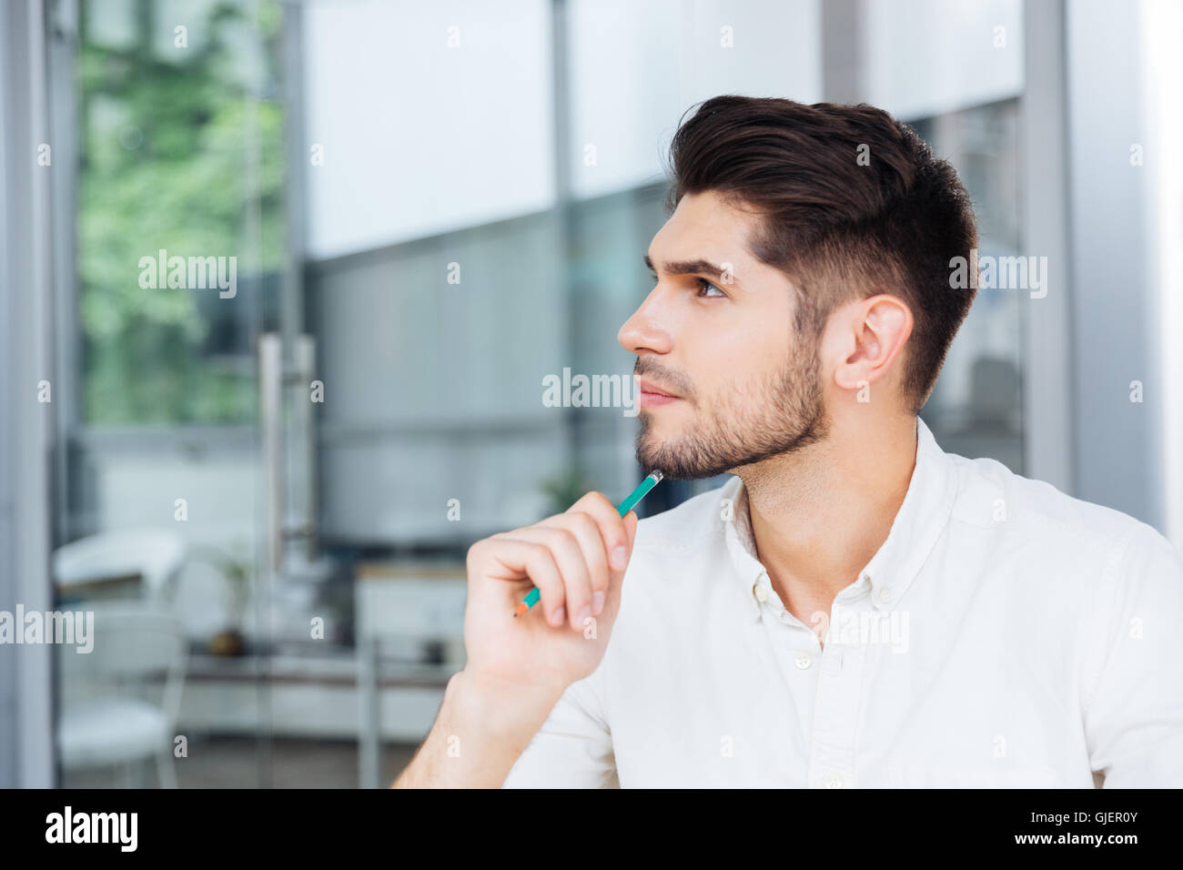 Handsome pensive young busineessman sitting and thinking in office - Stock Image