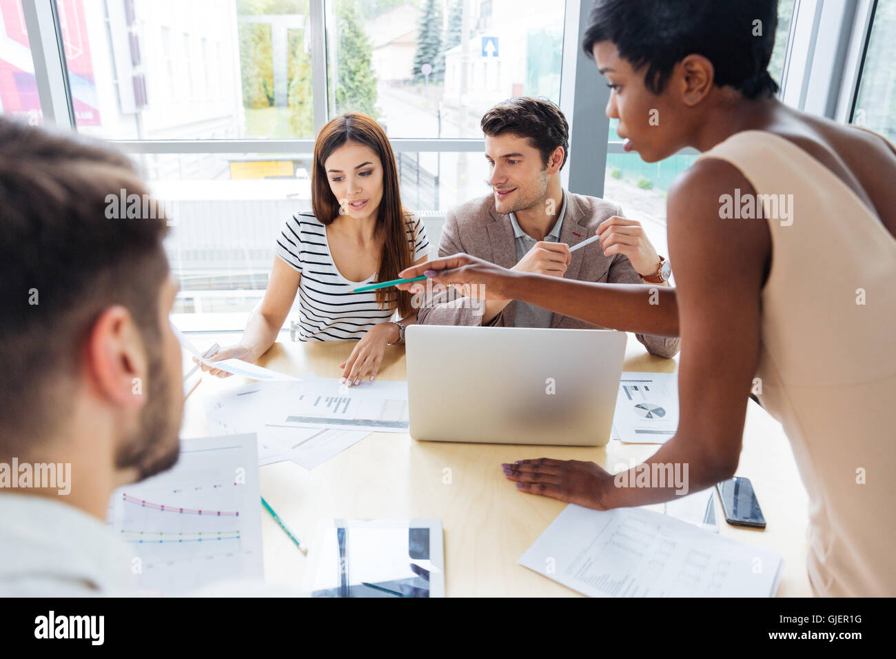 Multiethnic group of young business people preparing for presentation together in office - Stock Image