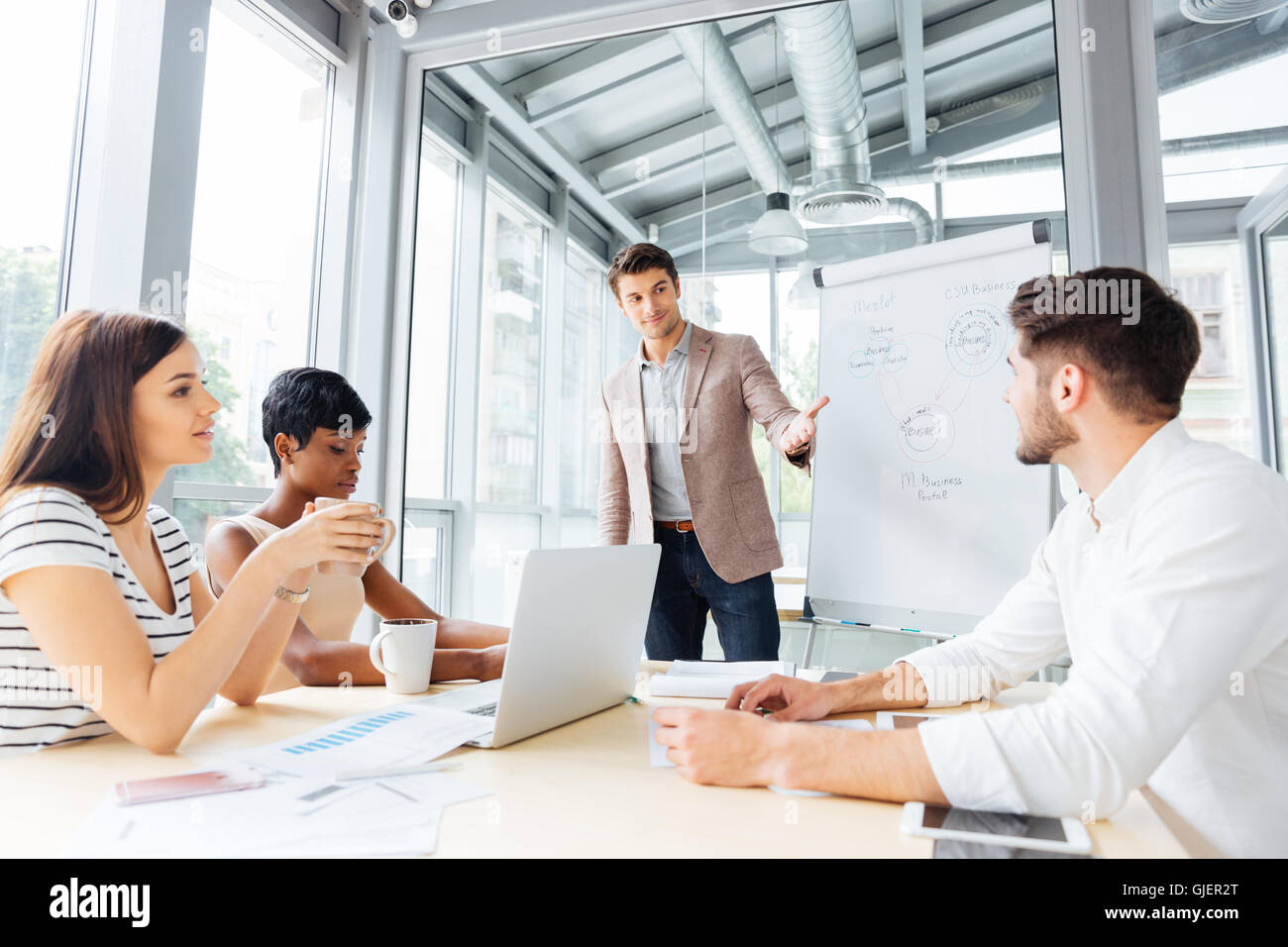 Successful young businessman making presentation of business plan using flipchart in office - Stock Image