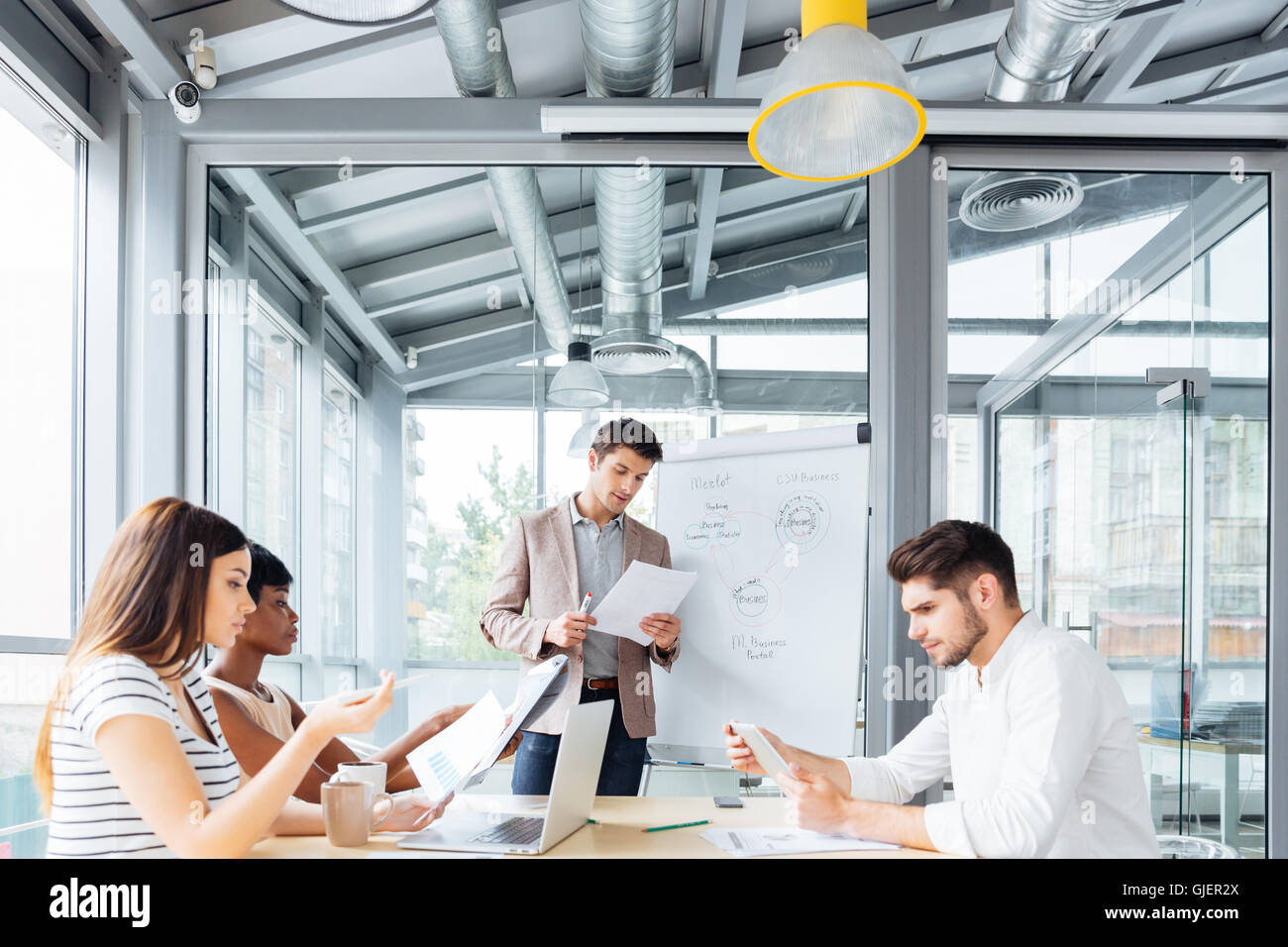 Concentrated young businessman giving presentation and reading documents in office - Stock Image